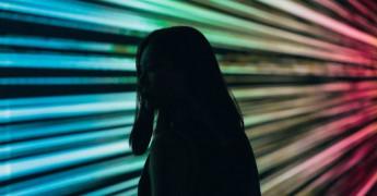 Voyeur, female silhouette over neon lights background