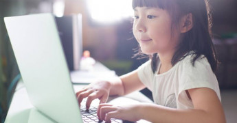 Child with laptop, typing on laptop