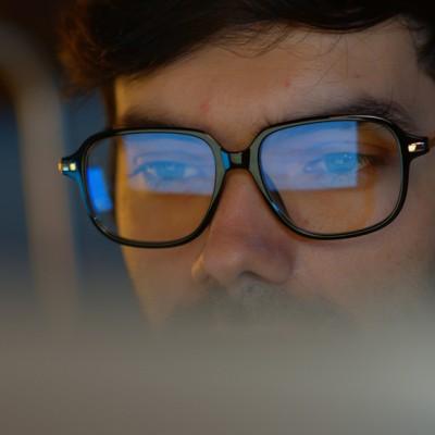 Employee wearing glasses reflecting computer screen