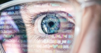 Computer code reflected in glasses on man, AI