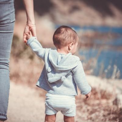 Mother holding baby's hand, children